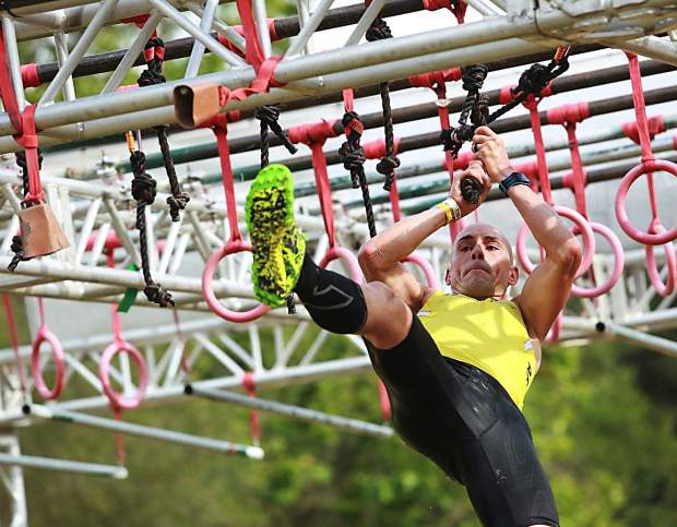 Robert Killian swing from ring to ring on an obstacle at a recent Spartan Race. The 12-year U.S. Army veteran is a former Ironman champion and winner of the Army's coveted