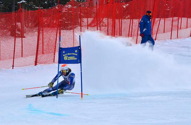 A Copper Mountain employee watches as a skier rounds the final gate of the flat section on the giant slalom course during the 2016 Surefoot FIS Colorado Ski Cup on Nov. 30. The annual event drew nearly 400 male and female ski racers from 23 nations for four days of GS and super-G racing.