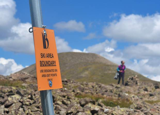 Frisco local Sara Skinner passes by a Breckenridge boundary sign marking the far north end of Peak Six (12,573 feet).