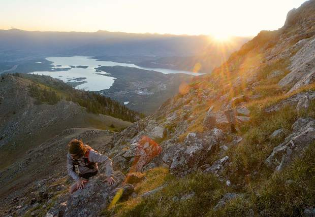 Ben Trollinger picks through a faint trail of boulders and tundra scrub as the sun rises on Peak One (12,805 feet), the first stretch of the Tenmile Traverse from Frisco to Breckenridge along the Tenmile Range.