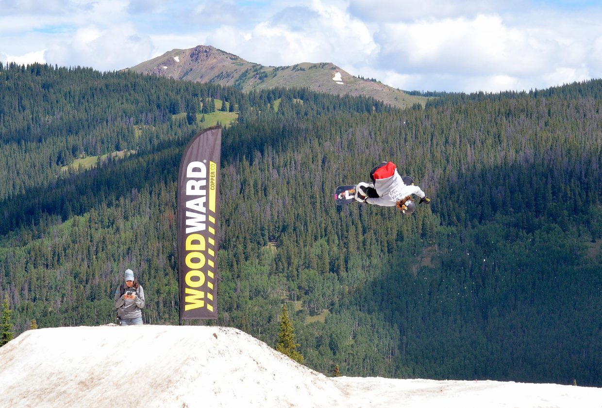 A snowboarder gets inverted with nothing but green trees in front and dirty snow below at the Woodward Copper summer snow park in July.