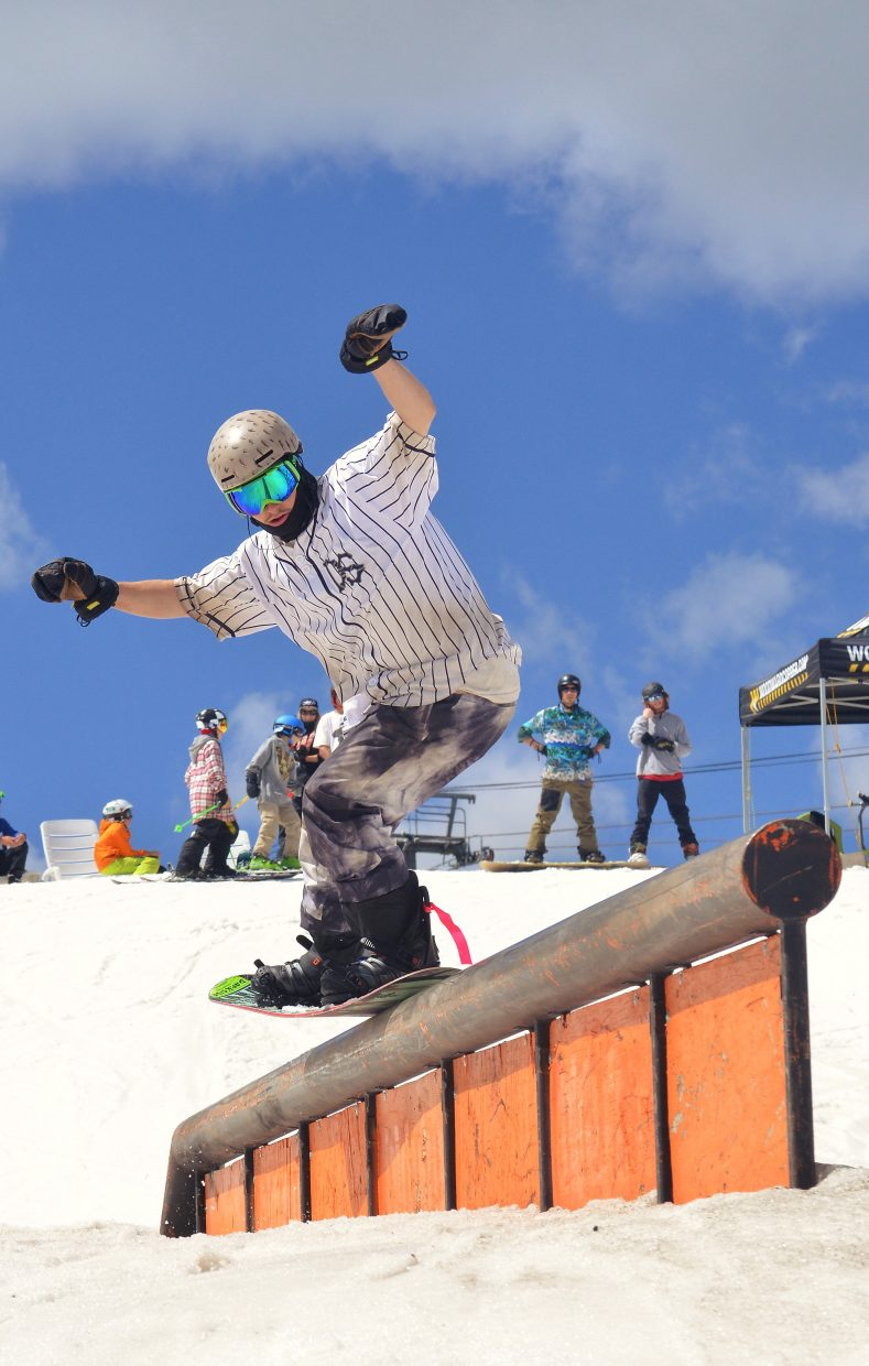A snowboarder leans into a nasty nosepress on the down tube feature at the Woodward Copper summer snow park in July.
