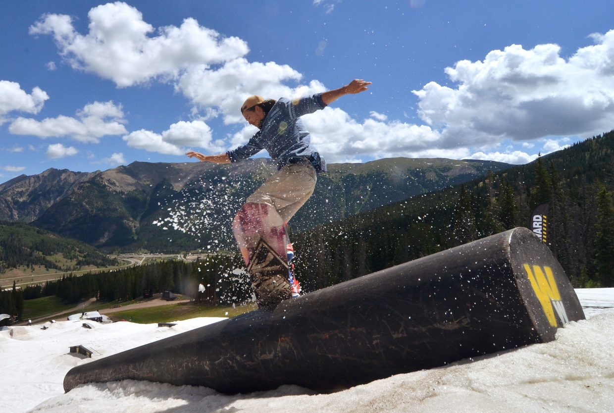 A snowboarder tweaks a noseblunt on the snowmaking tube feature at the Woodward Copper summer snow park in July.