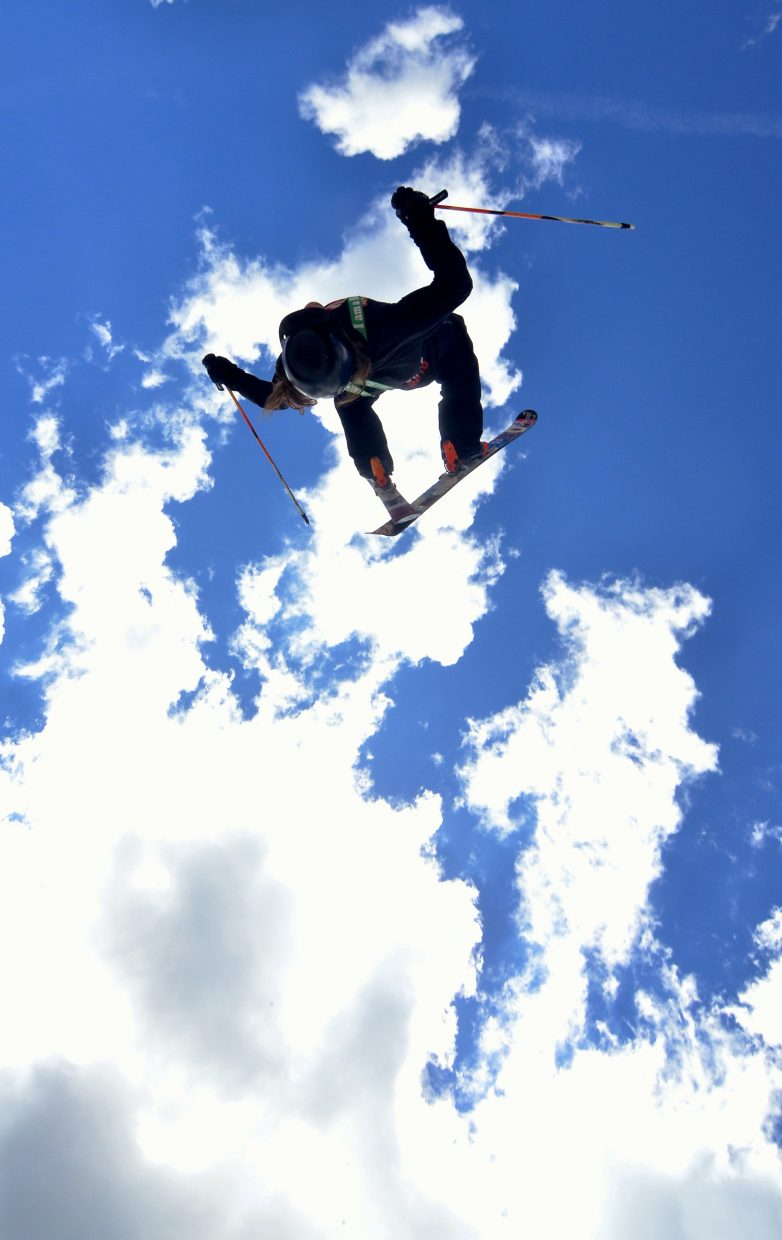 A Woodward Copper ski coach floats a switch backflip over the second jump in the three-pack line at the summer snow park on Copper Mountain.