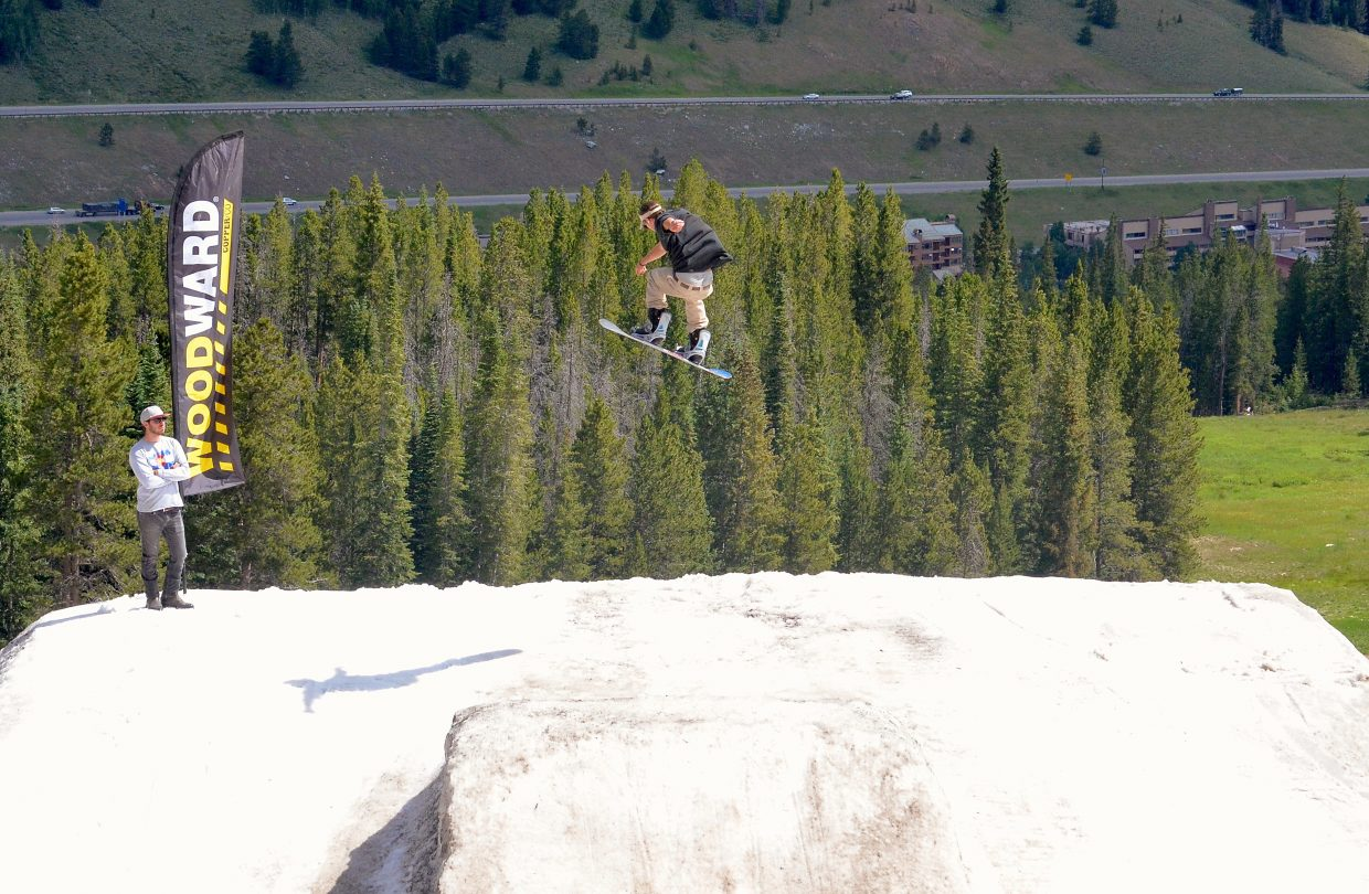 A snowboarder airs off the final (and largest) jump of the three-pack jump line at the Woodward Copper summer snow park with dry, mid-July trees in the background.