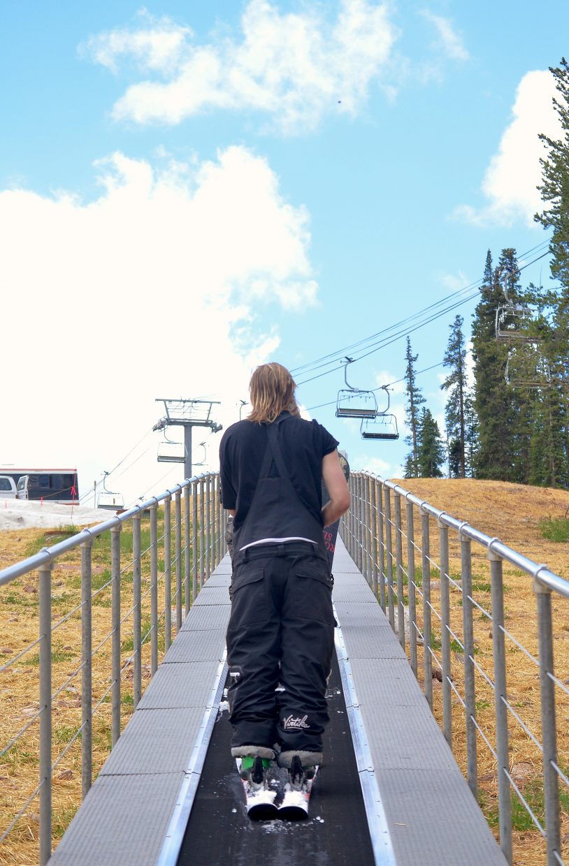 Skiers ride the brand-new carpet lift at Woodward Copper's summer snow park. In past years, campers had to wait for a van shuttle to lap the park or simply hike from feature to feature.