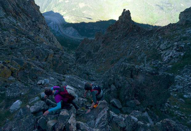 Local hikers Sara Skinner (purple) and Ben Trollinger drop down a rocky chute between Peak Three (12,676 feet) and Peak Four (12,866 feet) during an attempt of the Tenmile Traverse in August.