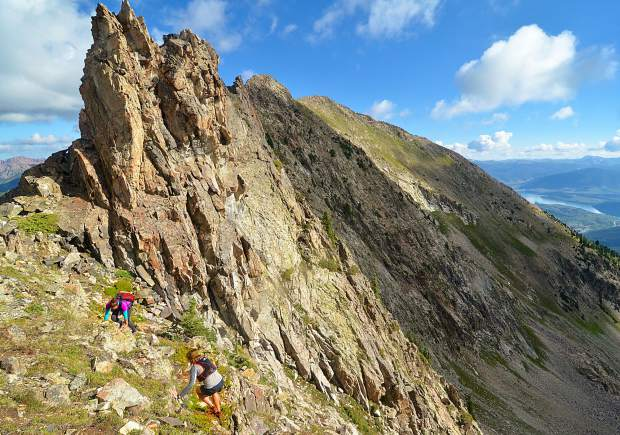 Local hikers Sara Skinner (purple) and Ben Trollinger pass by the Dragon's Teeth formation between Peak Three (12,676 feet) and Peak Four (12,866 feet) during an attempt of the Tenmile Traverse. The first stretch of the traverse is extremely exposed, with a combination of ridgeline scrambling and boulder fields.