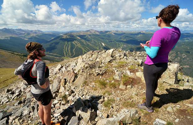 Local hikers Sara Skinner (purple) and Ben Trollinger stop for a snack and scenery at the summit of Peak Four (12,866) during an attempt of the Tenmile Traverse. The peak marks the end of precarious ridgeline scrambling and the start of long and unmarked ascents and descents through high-alpine tundra.