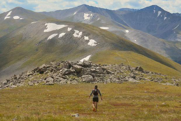 Summit Daily News managing editor Ben Trollinger hikes through high-alpine tundra on the Tenmile Range, with the rounded summit of Peak Five (12,855 feet) immediately in the background.