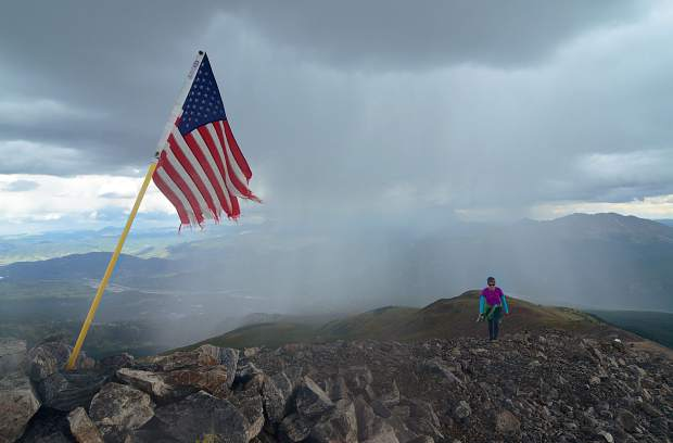 Frisco local Sara Skinner reaches the summit of Peak 10 (13,633 feet) as dark rainclouds form over the valley beneath Peak 9 (13,195 feet) on the final leg of the Tenmile Traverse. Our group completed the 14.5-mile traverse in just under 12 hours.