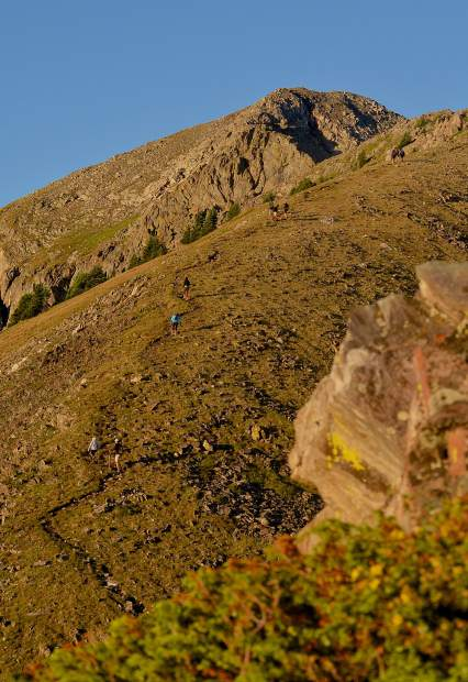 Tiny dots slowly move up a slice of singletrack on the final approach to Peak One (12,805 feet) near Frisco early on an August morning. The first stretch of the Tenmile Traverse follows a well-worn trail from Mount Royal to Peak One before the trail gives way to routefinding with cairns.