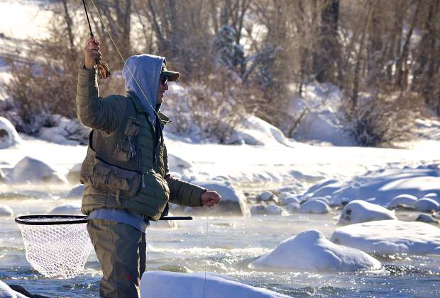 An angler casts on the Blue River below Dillon Dam in late December. The tail waters of the Dillon Dam are a favorite location for winter fly-fishing thanks to year-round midge hatching and small prey like Mysis shrimp.
