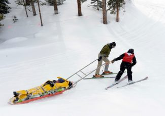 A Copper Mountain Ski Patrolman, right, along with an unidentified skier, pull an injured skier up a small hill on a patrol sled on the ride down to the St. Anthony Copper Mountain Clinic at the base of the mountain Friday, March 1st, 2013. Andy Cross, The Denver Post
