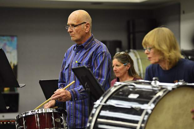 Husband and wife Bruce and Connie Anderson, right, play percussion insturments with Karen Kaminski, center, Thursday night at Summit High School.