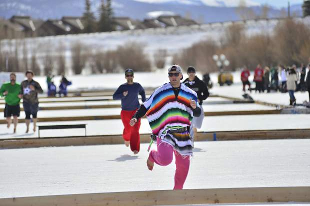 """""""That's cold,"""" a poncho-clad Jeff Bisping, of San Antonio, shouted after competing in a barefoot race across the pond Friday in Silverthorne."""