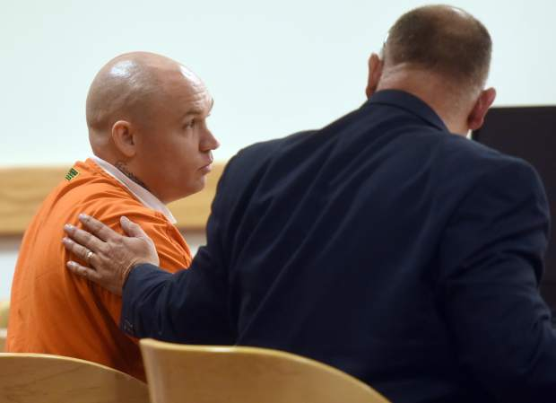 Defense attorney Jerry Manzer rests a hand on Paul Burman as his sentence is given on Wednesday at the Weld County Court House in Greeley. Burman was sentenced to 248 years in prison for human trafficking, pimping women and underage girls, in addition to several other charges.