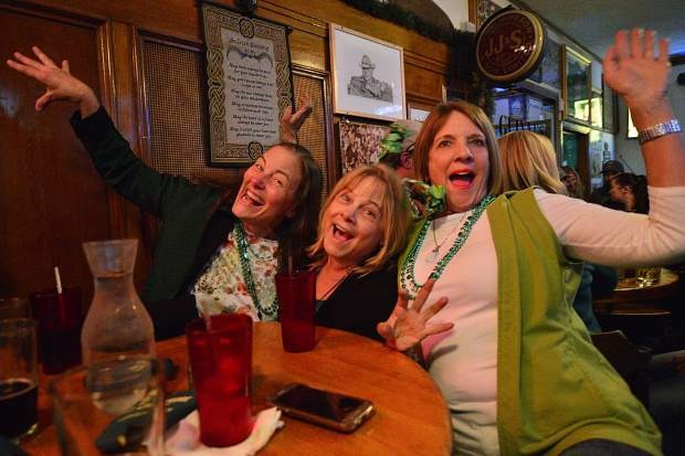 From left, Katy Abbott, Hesh Diguiseppi and Kathy Alexander of Denver throw their arms in the air as they came up to the mountains Friday night to party down on St. Patrick's Day at Murphy's Irish Pub in Silverthorne.