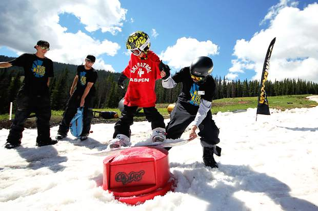 A young snowboarder gets instruction with Woodward Copper coaches during a summer on-snow camp session.