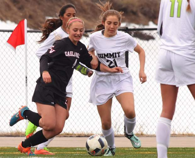 Summit freshman Nicole Kimball (21) bumps up with Eagle Valley's Jessica Adams (4) at a home varsity soccer game on March 21. The Tigers lost, 1-3.