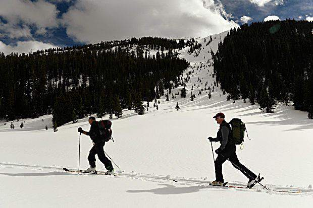 Patrick O'Sullivan, Director of Risk and Safety, left, and Alan Henceroth, Chief Operating Officer at Arapahoe Basin, right, take the hike-out trail on skis and skins after skiing The Beavers in February 2016. Arapahoe Basin will begin installing lift towers and clearing runs in the area this summer, with an opening for the 468-acre expansion set for the 2017-18 ski season.