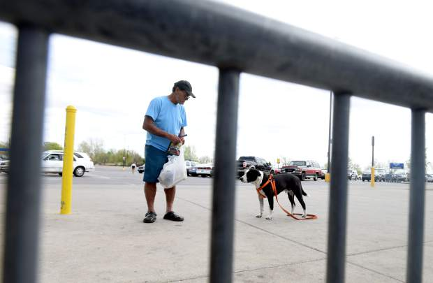 John Delgado glances back at his dog, Cash, as they walk through the Wal-Mart parking lot in Evans. He's rarely ever separated from his dog.