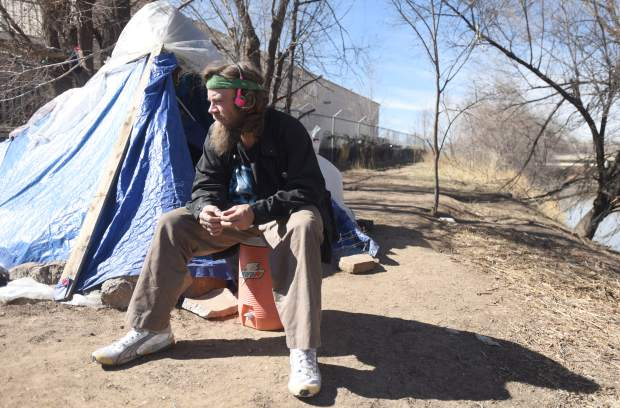 Wesley Waldvogle sits outside of his makeshift home along the Poudre River this past month in Greeley.