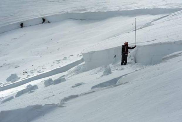 Scott Toepfer, right, a member of the Colorado Avalanche Information Center, takes depth measurements after a deadly avalanche in April 2013 near Loveland Pass. In the background, fellow forecasters Brian Lazar and John Snook investigate layers in the snowpack.