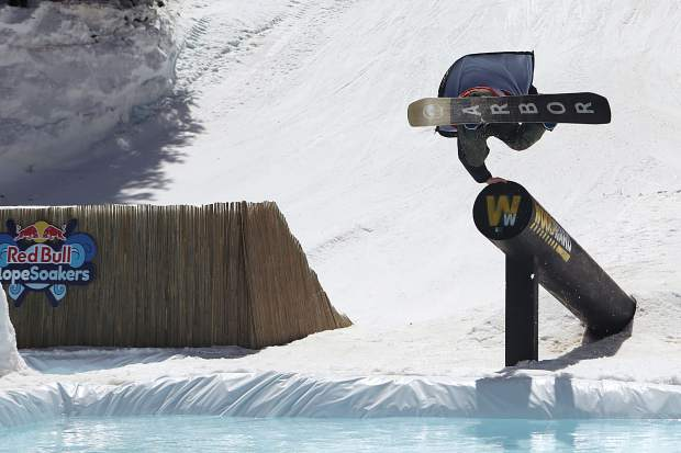 A snowboarder tries for a handplant off the shooter pipe during the 2017 Red Bull Slopesoakers pond-skimming rail jam on April 15 at Copper Mountain.