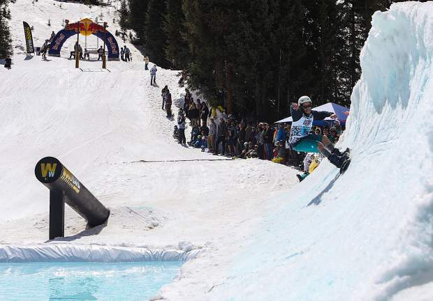 A snowboarder rides the snow wave over the water waves below during the 2017 Red Bull Slopesoakers pond-skimming rail jam on April 15 at Copper Mountain.