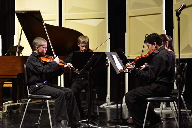 """With Malachi Ryan, center left, Isabella Huhn, back right, and Isaac Webster, right, Caleb Arthurholt performs his original composition, """"Quartet for Violins,"""" during the third annual Young Composers Competition Concert on Monday at Summit Middle School in Frisco."""