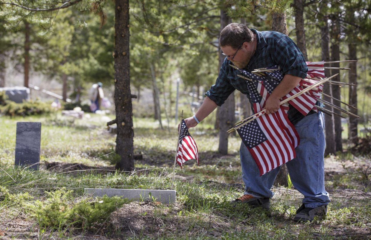 Kelly Crangle places an american flag at a veterans grave site during the annual Memorial Day of Remembrance Ceremony Monday, May 29, 2017, at the Dillon Cemetery in Dillon. The previous year's flags are replaced every year on Memorial Day with new ones at each veteran burial site in the cemetery.