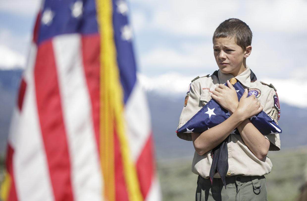 Summit County Boy Scout troop member Dominick Leonardo holds onto the folded flag during the annual Memorial Day of Remembrance Ceremony Monday, May 29, 2017, at the Dillon Cemetery in Dillon.