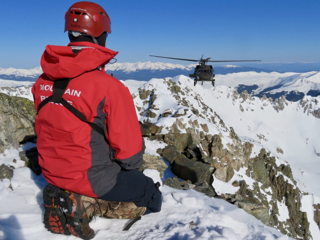 A Summit County Rescue Group members looks on as a Blackhawk helicopter approaches Quandary Peak.