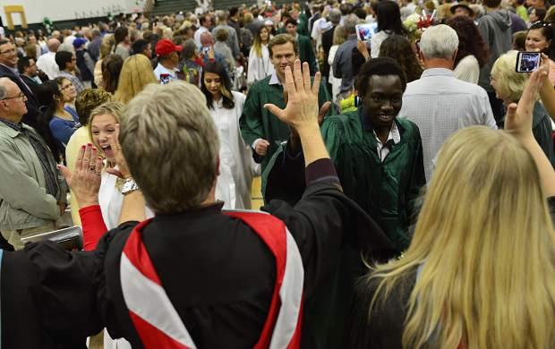 Summit High School faculty members give members of the Class of 2017 high fives as the graduated seniors file out of the gymnasium at the conclusion of their graduation ceremony on Saturday.
