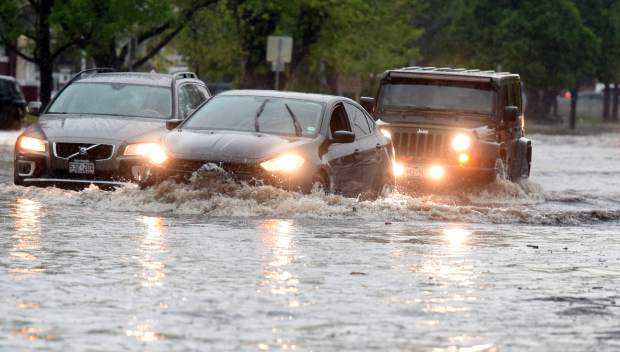 Cars struggle through some of the deeper water at the intersection of 10th Street and 11th Avenue on Monday in downtown Greeley.