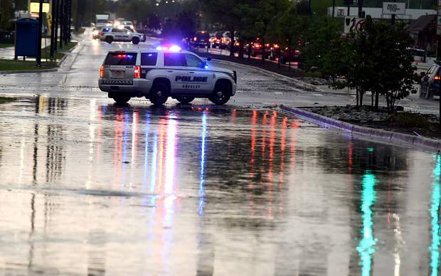 A police car blocks traffic in front of some of the high water that snarled traffic on 10th Street on Monday in Greeley.