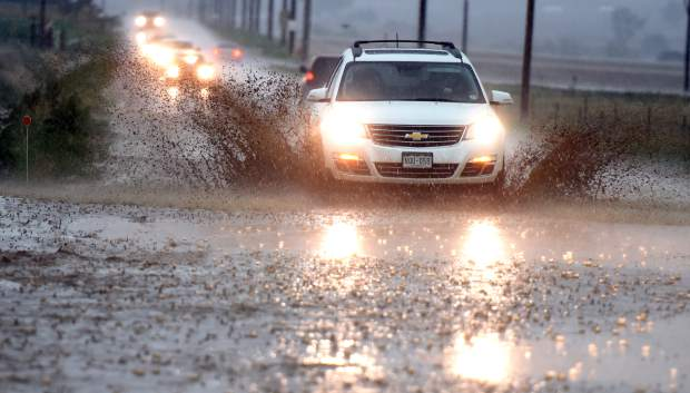 Cars drive through the muddy water that has spilled onto the roads on 83rd Avenue in west Greeley.