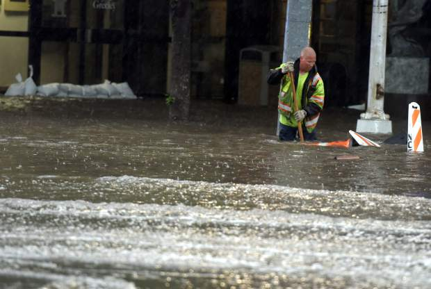 A city worker tries to grab the caution barrels and cones that are floating away as rain continues to fall and roads flood on Monday in downtown Greeley. About 1.5 inches of rain fell in Greeley Monday during a 20-minute period, causing widespread flash flooding.