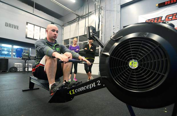 Crossfit coach Nick Keene (front) demonstrates proper rowing technique to an acclimation class at Crossfit Low Oxygen in Frisco. Rowing is a perfect gym routine for kayakers, rafters and stand-up paddleboard athletes who want to get conditioned before summer arrives in full.