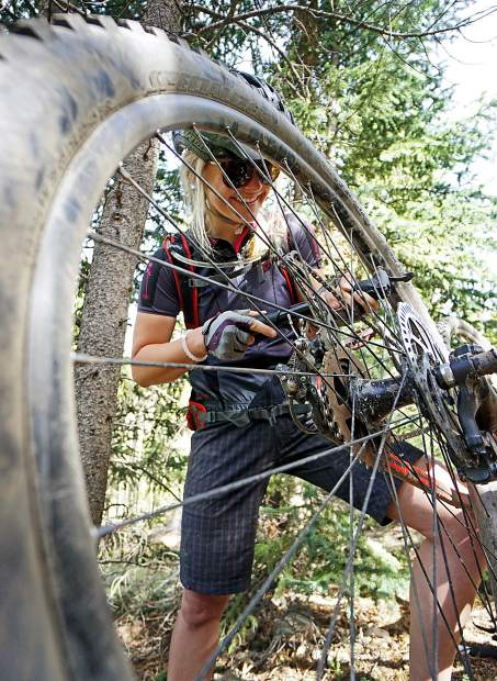 Katie Damby does a little trailside maintenance on Lower Flume trail, Breckenridge. Avoid trail-side repairs this May and June with pre-season maintenance on your mountain bike and road bike.