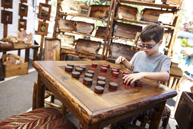 Cristiano Dimeo, 8, of Florida, plays with a wooden checkers set up at The Cabin Collection vendor during Dillon Farmers Market Friday, June 23, on Buffalo Street in Dillon.