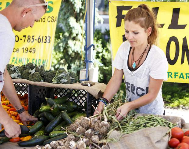 Melissa Miller, right, and Joshua Howard restock fresh vegetables at their selling table during Dillon Farmers Market Friday, June 23, on Buffalo Street in Dillon.
