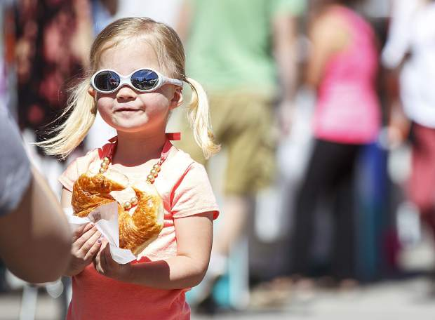 Summit County resident Sawyer Konkle, 3, poses for her monther's photo with a croissant bought at Dillon Farmers Market Friday, June 23, on Buffalo Street in Dillon.
