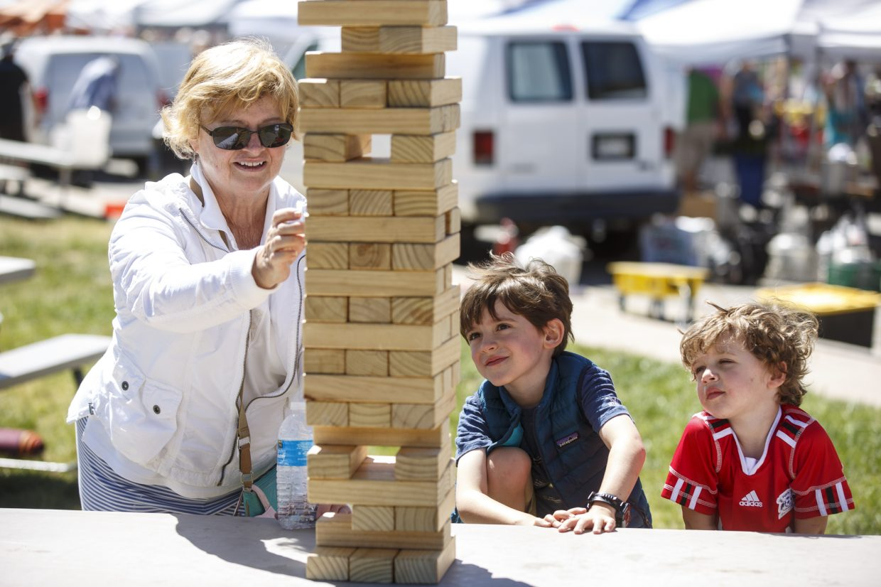 Wilson, 5, and Jack Denton, 2, watches as their grandma, Toni Wilson, of Little Rock, Ark., carefully picks out a piece of Jenga block during Dillon Farmers Market Friday, June 23, on Buffalo Street in Dillon.