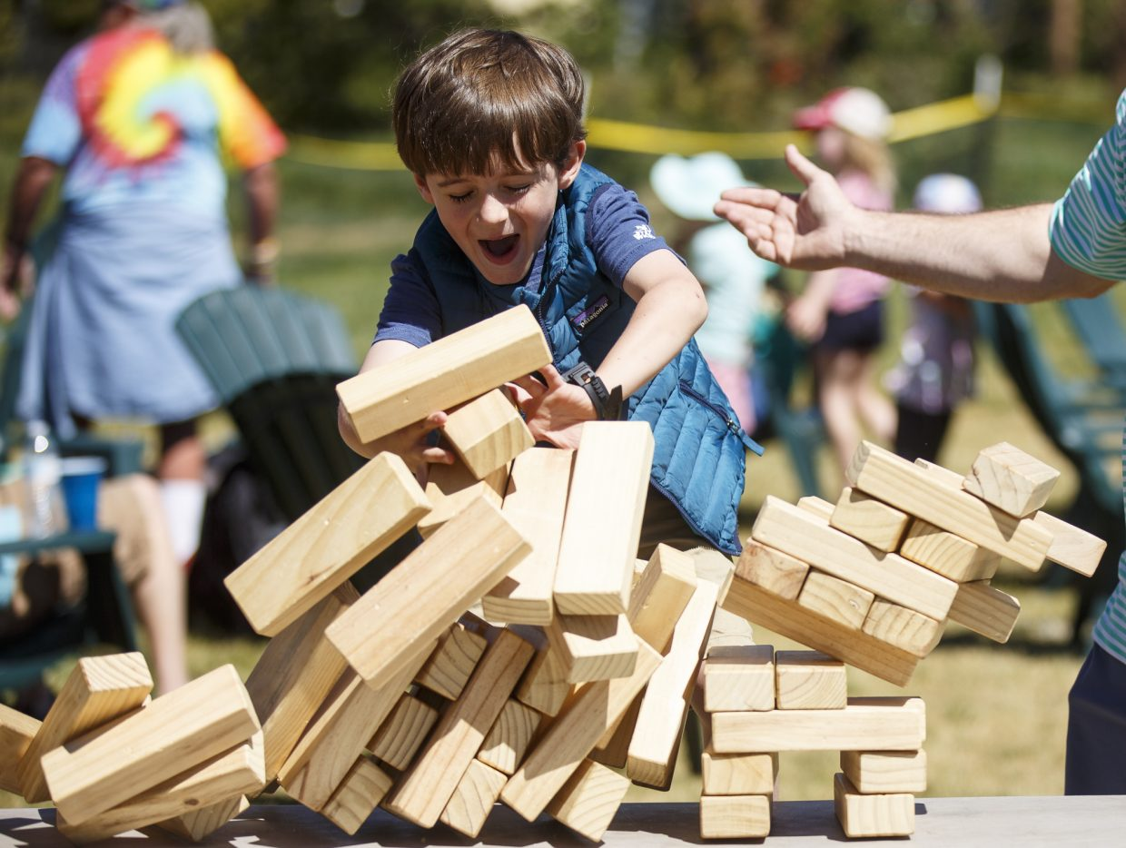 Wilson Denton, 5, reacts as Jenga block pieces tumble during Dillon Farmers Market Friday, June 23, on Buffalo Street in Dillon.