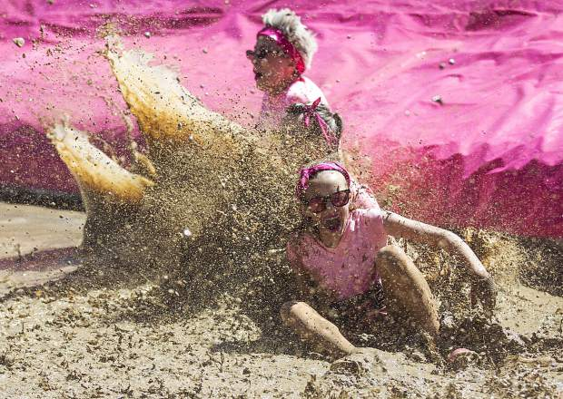 A duo in the 2017 Dirty Girl Mud Run gets a taste of mud at one of more than a dozen features at Copper Mountain on June 10. The event drew hundreds of female runners from across the state and globe for a 5K benefit to support Boarding for Breast Cancer, a California nonprofit that pairs breast cancer survivors with snowboarding, skateboarding, surfing and mud running.