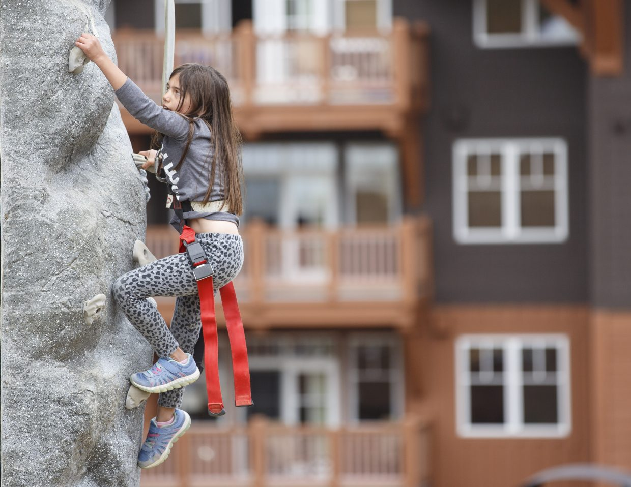 Liviana Olivetti, 7, of Denver, climbs up the