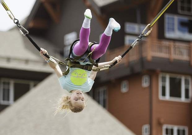Pipper Tarrant, 8, flips on a bungee trampoline during the opening day of Epic Discovery summer theme park Friday June 9, on Breckenridge Ski Resort.