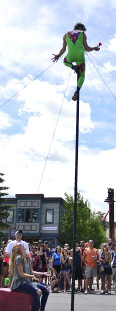 Derek McAlister does stunts as he climbs up and slides down an 18-foot pole Saturday at the Frisco BBQ Challenge. McAlister has spent most of his life developing the skills necessary to put on these shows, and he said he hopes people keep an open mind to street performers and see them as the professionals they are, not bums merely asking for money.